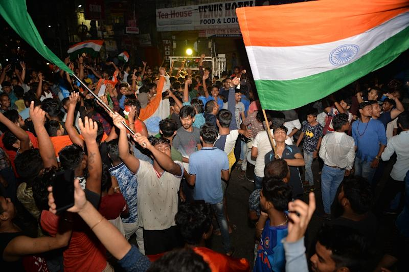 Supporters of the Indian cricket team wave national flags as they celebrate in Siliguri after the win against Pakistan (AFP Photo/DIPTENDU DUTTA)