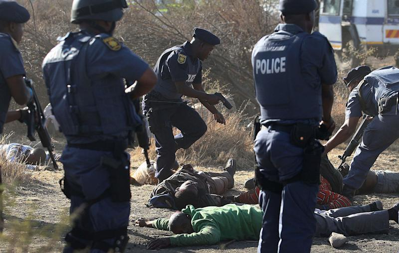 RETRANSMISSION FOR ALTERNATIVE CROP Police surround the bodies of striking miners after opening fire on a crowd at the Lonmin Platinum Mine near Rustenburg, South Africa, Thursday, Aug. 16, 2012. South African police opened fire Thursday on a crowd of striking workers at a platinum mine, leaving an unknown number of people injured and possibly dead. Motionless bodies lay on the ground in pools of blood. (AP Photo)