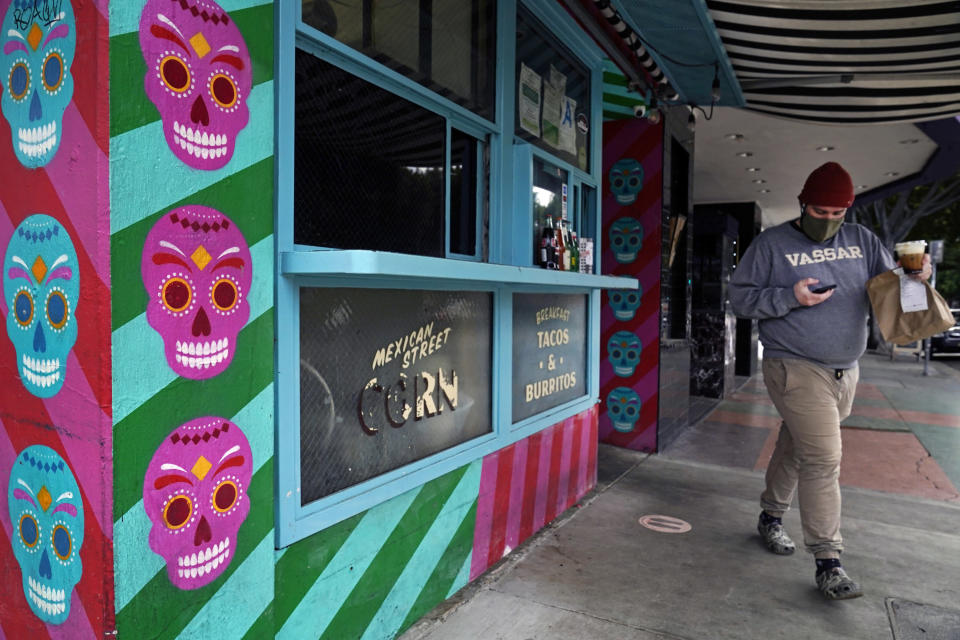 "A person picks up food to go at ""Tacos Tu Madre,"" restaurant in Los Angeles Monday, Jan. 25, 2021. California has lifted regional stay-at-home orders statewide in response to improving coronavirus conditions. Public health officials said Monday that the state will return to a system of county-by-county restrictions intended to stem the spread of the virus. Local officials could choose to continue stricter rules. The state is also lifting a 10 p.m. to 5 a.m. curfew. (AP Photo/Damian Dovarganes)"