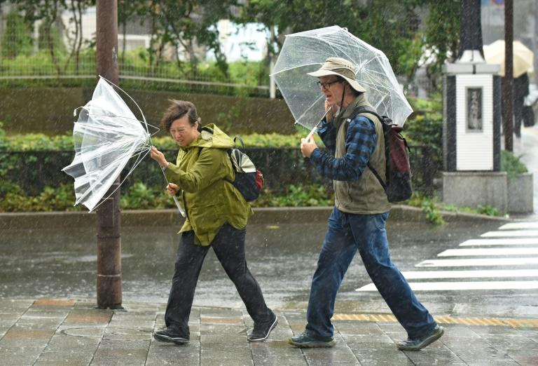 "Voters in the capital braved torrential rain and driving wind on election day, as a projection from NHK said Abe's ruling conservative coalition was on track to win a two-thirds ""super-majority"""
