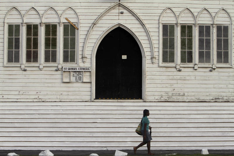 A woman walks past the St. George Cathedral in Georgetown, Guyana, Thursday, Nov. 25, 2010. Guyana will host the fourth regular summit of the UNASUR, Union of South American Nations, on Nov. 26 (AP Photo/Arnulfo Franco)