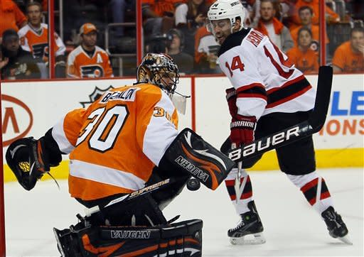 Philadelphia Flyers' Ilya Bryzgalov, left, deflects a shot as New Jersey Devils' Adam Henrique tries for the rebounding puck during the first period in Game 2 of an NHL hockey Stanley Cup second-round playoff series, Tuesday, May 1, 2012, in Philadelphia. (AP Photo/Tom Mihalek)