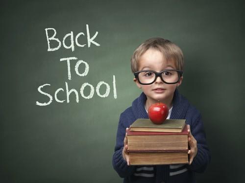Boy with books and apple in front of chalkboard reading 'Back To School'