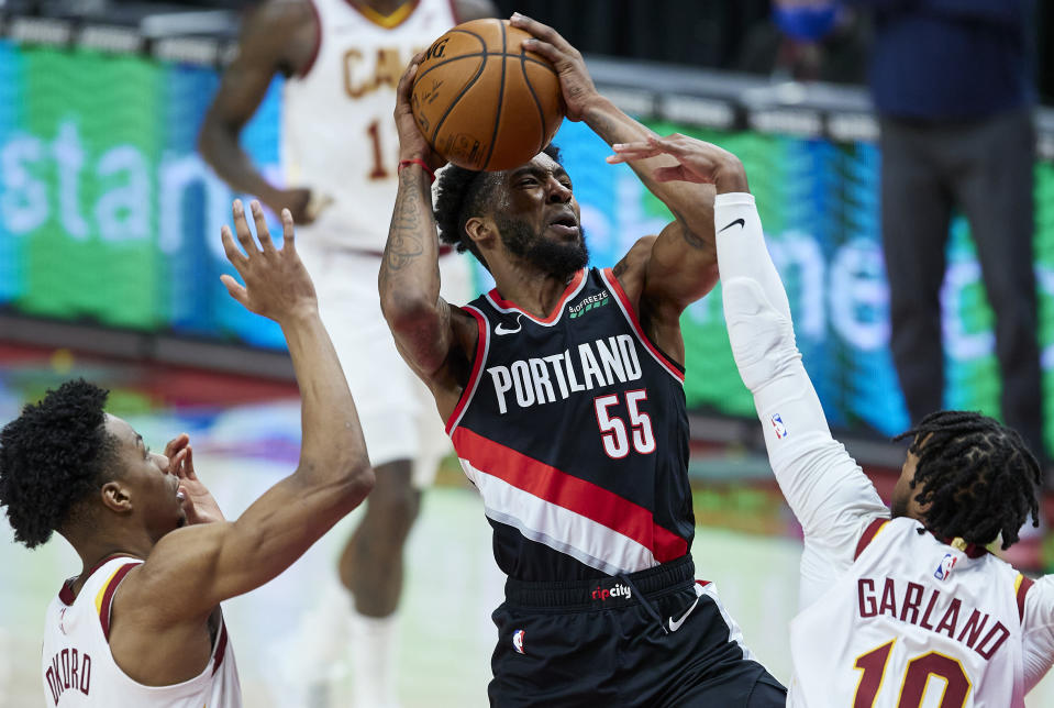 Portland Trail Blazers forward Derrick Jones Jr., center, drives to the basket between Cleveland Cavaliers guards Darius Garland, right, and Isaac Okoro during the second half of an NBA basketball game in Portland, Ore., Friday, Feb. 12, 2021. (AP Photo/Craig Mitchelldyer)