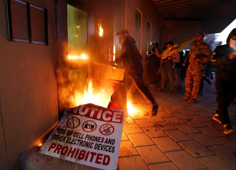 Protesters and militia fighters set fire to a reception room of the U.S. Embassy, during a protest to condemn air strikes on bases belonging to Hashd al-Shaabi, in Baghdad