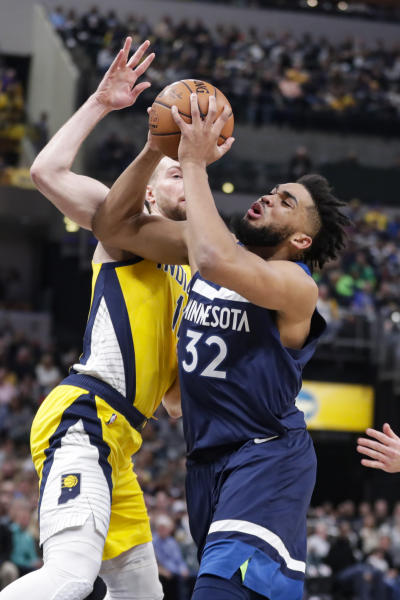 Minnesota Timberwolves center Karl-Anthony Towns (32) shoots in front of Indiana Pacers forward Domantas Sabonis (11) during the first half of an NBA basketball game in Indianapolis, Friday, Jan. 17, 2020. (AP Photo/Michael Conroy)