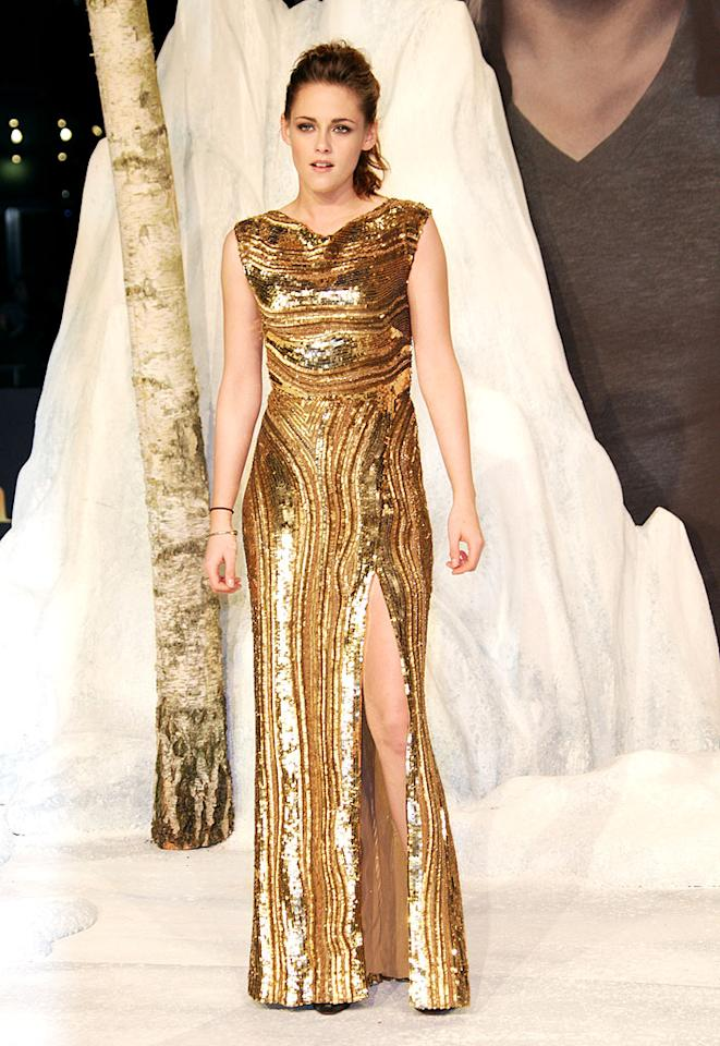"We are so used to seeing Kristen Stewart in Converse sneakers and hooded sweatshirts that we were dazzled by her glam turn during the press tour for ""The Twilight Saga: Breaking Dawn – Part 2."" The highlight was this glittery gold Elie Saab dress, which she wore to the German premiere. The high-waisted gown boasted a vertical pattern on the skirt, which elongated her body, and a thigh-high slit showing off her gams. Very ""Kristen"" though was her hair – pulled back in a loose ponytail – with her hair tie worn on her wrist. Also, later in the evening she ditched her Christian Louboutin open toe booties for ... black sneakers. (11/16/2012)"