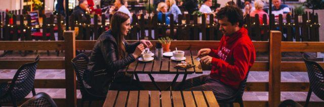 photo of young man and woman on date sitting at table facing each other