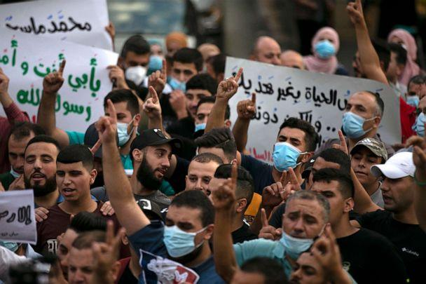 PHOTO: Palestinians hold banners during a protest against French President Macron's remarks on the cartoons of the Prophet Mohammed, in the West Bank city of Ramallah, Oct. 27, 2020. (Abbas Momani/AFP via Getty Images)