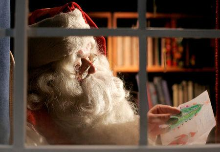 FILE PHOTO: A man dressed as Santa Claus reads letters from children from around the world in his office at  the Santa Claus' Village at the Arctic Circle near Rovaniemi, Finland December 18, 2007. REUTERS/Kacper Pempel/File Photo