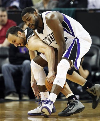 San Antonio Spurs forward Manu Ginobili, of Argentina, left, and Sacramento Kings guard Tyreke Evans scramble for the ball during the first quarter of an NBA basketball game in Sacramento, Calif., Wednesday, March 28, 2012. (AP Photo/Rich Pedroncelli)