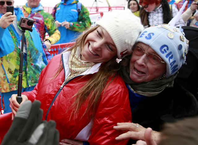 Women's supercombined bronze medal winner United States' Julia Mancuso and her grandmother Sheila Tuffanelli are surrounded by well-wishers at the Alpine ski venue at the Sochi 2014 Winter Olympics, Monday, Feb. 10, 2014, in Krasnaya Polyana, Russia. (AP Photo/Gero Breloer)