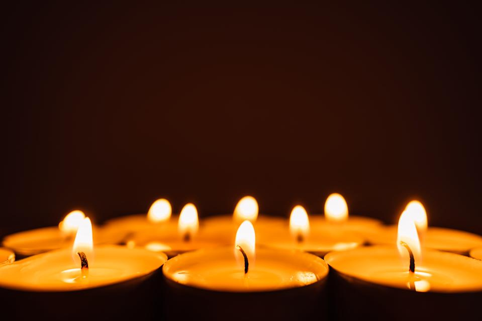 Burning candles in a row in the dark with copy space.