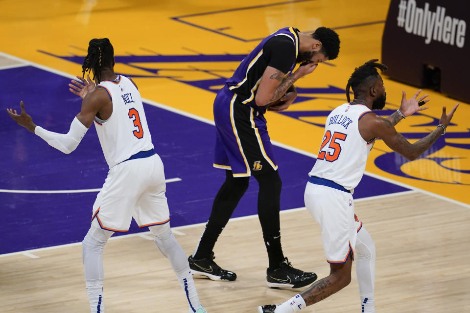 Los Angeles Lakers forward Anthony Davis, center, reacts after getting hit in the face by New York Knicks center Nerlens Noel (3) during the fourth quarter of an NBA basketball game Tuesday, May 11, 2021, in Los Angeles. New York Knicks forward Reggie Bullock (25) is at right. (AP Photo/Ashley Landis)