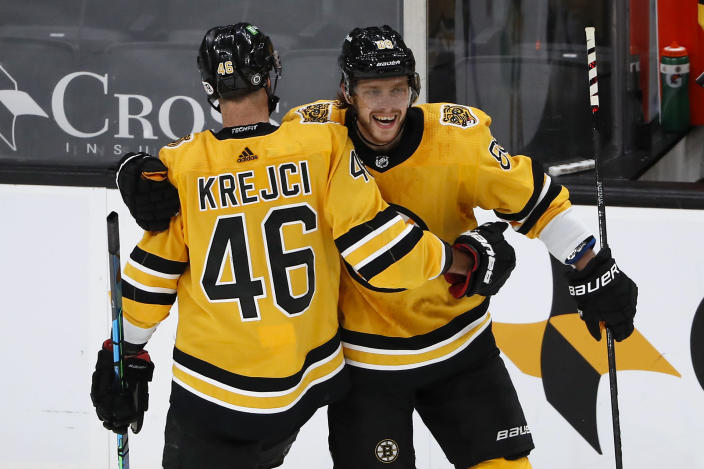 Boston Bruins David Krejci congratulates David Pastrnak after Pastrnak scored against the Pittsburgh Penguins during the second period of an NHL hockey game Saturday, April 3, 2021, in Boston. (AP Photo/Winslow Townson)