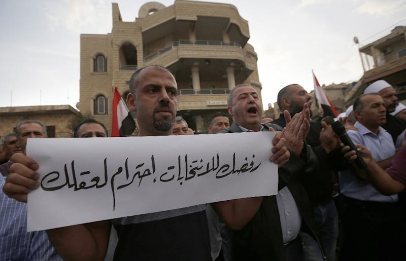 Residents of Majdal Shams on the Israeli-annexed Golan Heights, holding Syrian flags, demonstrate against taking part in municipal elections (AFP Photo/JALAA MAREY)
