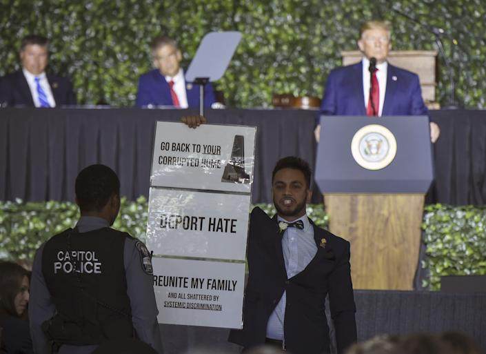 Virginia State Delegate Ibraheem Samirah holds a sign as President Trump speaks in Jamestown, Va., on July 30. (Photo: Andrew Caballero-Reynolds/AFP/Getty Images)