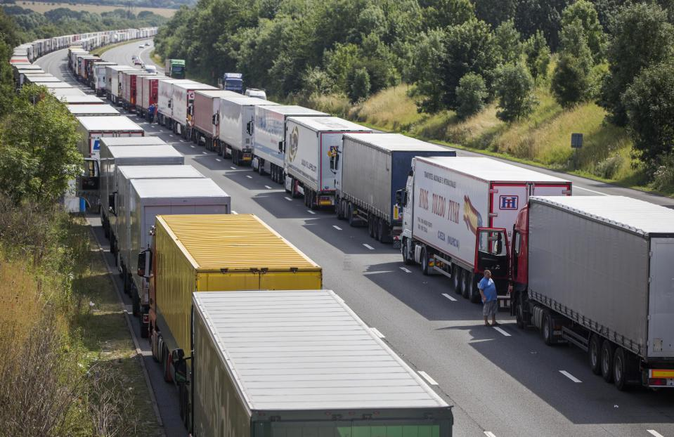 Drivers wait next to their parked lorries on the M20 motorway, which leads from London to the Channel Tunnel terminal at Ashford and the Ferry Terminal at Dover, as part of Operation Stack in  southern England, Britain July 31, 2015. Prime Minister David Cameron drew up plans to help France tackle a spike in attempts by migrants to enter Britain illegally via the Channel Tunnel, but warned there was no quick fix. Cameron is under pressure to deter the migrants, many of whom have travelled from Africa and the Middle East, after disruption to cross-Channel passenger and freight traffic. REUTERS/Neil Hall