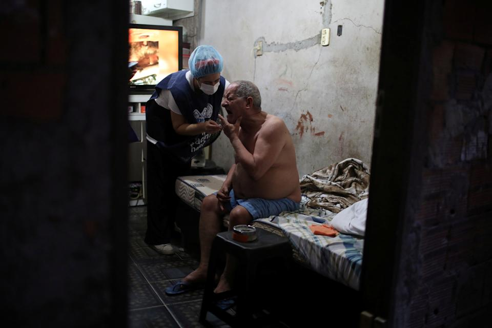 Carlos Alberto Tabares de Oliveira, 64, gestures as he receives the AstraZeneca coronavirus disease (COVID-19) vaccine at home, as healthcare workers administer the vaccine to elderlies who cannot leave home, in the Rocinha slum in Rio de Janeiro, Brazil April 16, 2021. REUTERS/Pilar Olivares     TPX IMAGES OF THE DAY