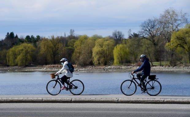 Masked cyclists make their way along the edge of Dows Lake on April 13, 2021, as the third wave of the COVID-19 pandemic grips Ottawa. (Sean Kilpatrick/Canadian Press - image credit)