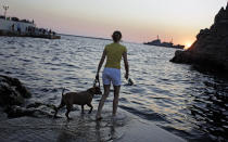 """FILE - In this Saturday, July 24, 2010 file photo, a girl plays with her dog in Sevastopol, Ukraine. Despite the pebble beaches and cliff-hung castles that made Crimea famous as a Soviet resort hub, the Black Sea peninsula has long been a corruption-riddled backwater in economic terms. The Kremlin, which decided to take the region from Ukraine after its residents voted in a referendum to join Russia, has begun calculating exactly what it will cost to support Crimea's shambolic economy _ which one Russian minister described as """"no better than Palestine."""" (AP Photo/Sergey Ponomarev, File)"""