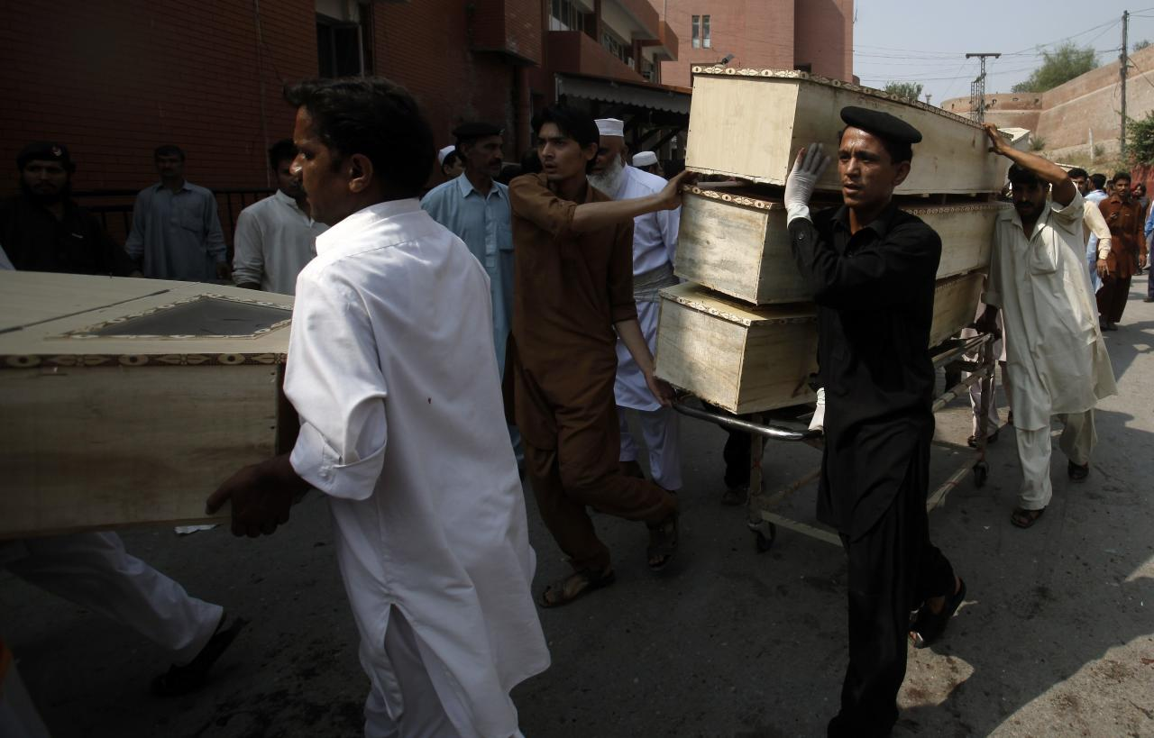Hospital staff carry coffins after a bomb blast, at a hospital in Peshawar September 29, 2013. Twin blasts in the northwestern Pakistan city of Peshawar killed 33 people and wounded 70 on Sunday, a week after two bombings at a church in the frontier city killed scores, police and hospital authorities said.REUTERS/ Fayaz Aziz (PAKISTAN - Tags: CIVIL UNREST POLITICS CRIME LAW)