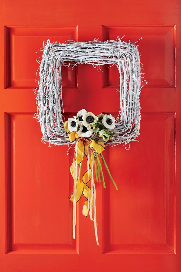 <p>Transform a simple square grapevine wreath with a layer of white spray paint and a small round florist foam cage (secured with wire to the bottom of the wreath). This version is filled with springy white anemones, but you can insert any flower into the foam and finish with a pinning of Spanish moss and flowy ribbons.</p>