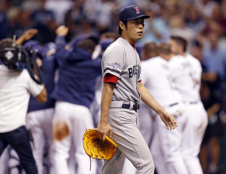 Boston Red Sox's relief pitcher Koji Uehara walks away as the Tampa Bay Rays celebrate the game winning home run by Jose Lobaton in the ninth inning in Game 3 of an American League baseball division series, Monday, Oct. 7, 2013, in St. Petersburg, Fla. (AP Photo/Mike Carlson)