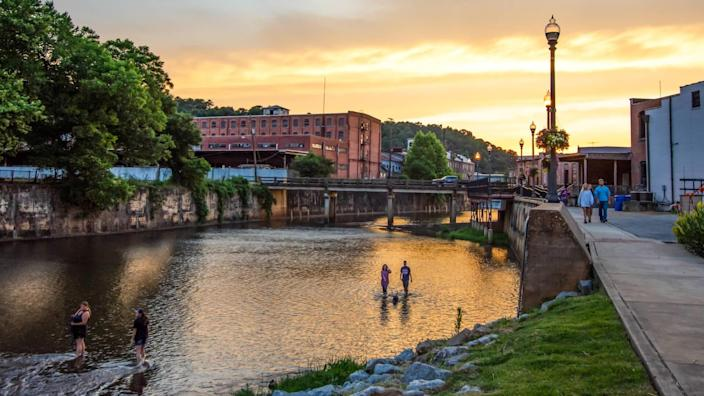 Prattville, Alabama/USA-June 12, 2019: A scenic view of people enjoying Autauga Creek and the Creekwalk area of Prattville during a beautiful golden sunset on a warm summer evening.