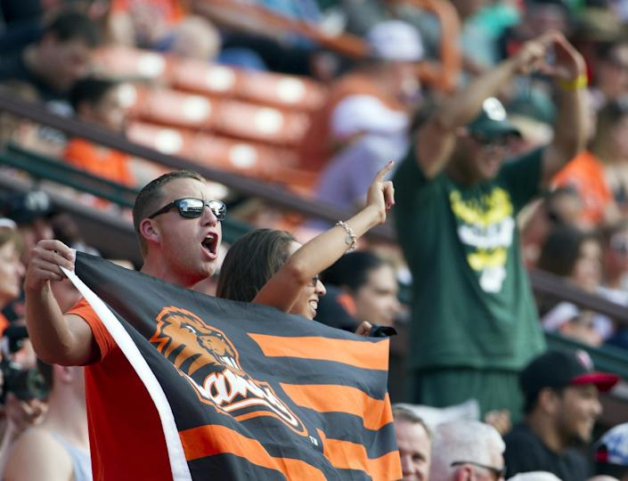 Oregon State fans cheer on their team in the first quarter of the Hawaii Bowl NCAA college football game, in Honolulu, Tuesday, Dec. 24, 2013. (AP Photo/Eugene Tanner)