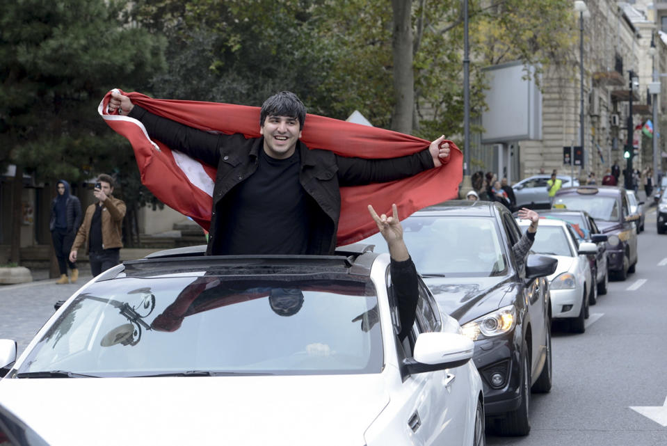 Azerbaijani man with the national flag celebrates after the country's President claimed Azerbaijani forces have taken Shushi, a key city in the Nagorno-Karabakh region that has been under the control of ethnic Armenians for decades in Baku, Azerbaijan, Sunday, Nov. 8, 2020. (AP Photo)