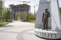 A sculpture commemorating the Tulsa Race Massacre stands in John Hope Franklin Reconciliation Park in Tulsa, Okla., Wednesday, April 14, 2021, with new construction in the background. (AP Photo/Sue Ogrocki)