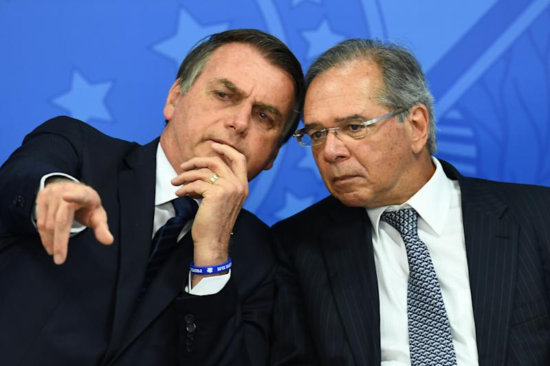 Brazilian President Jair Bolsonaro (L) and his Finance Minister Paulo Guedes talk during the inauguration ceremony of Gustavo Montezano as the new president of the National Bank for Economic and Social Development (BNDES) in Brasilia on July 16, 2019. (Photo by EVARISTO SA / AFP) (Photo credit should read EVARISTO SA/AFP via Getty Images)