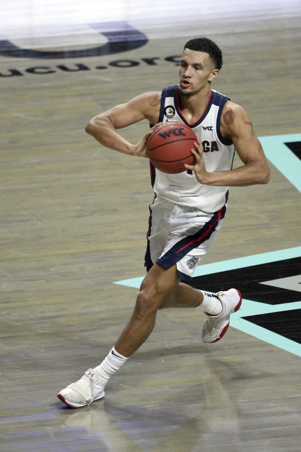 Gonzaga guard Joel Ayayi (11) looks to pass the ball against Saint Mary's during the first half of an NCAA semifinal college basketball game against Saint Mary's at the West Coast Conference tournament Monday, March 8, 2021, in Las Vegas. (AP Photo/David Becker)