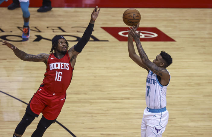 Charlotte Hornets guard Malik Monk (1) shoots as Houston Rockets guard Ben McLemore (16) defends during the second quarter of an NBA basketball game Wednesday, March 24, 2021, in Houston. (Troy Taormina/Pool Photo via AP)