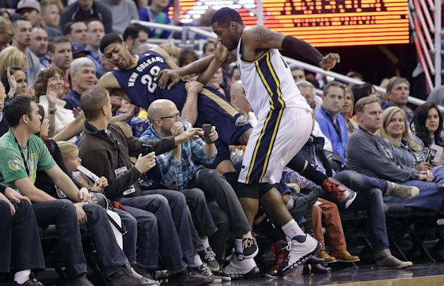Utah Jazz's Derrick Favors, right, and New Orleans Pelicans' Anthony Davis (23) crash in to the fans in the second quarter during an NBA basketball game on Friday, April 4, 2014, in Salt Lake City. (AP Photo/Rick Bowmer)