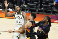 Milwaukee Bucks forward Khris Middleton (22) is defended by Phoenix Suns guard Devin Booker, middle, and forward Jae Crowder during the second half of Game 5 of basketball's NBA Finals, Saturday, July 17, 2021, in Phoenix. (AP Photo/Matt York)