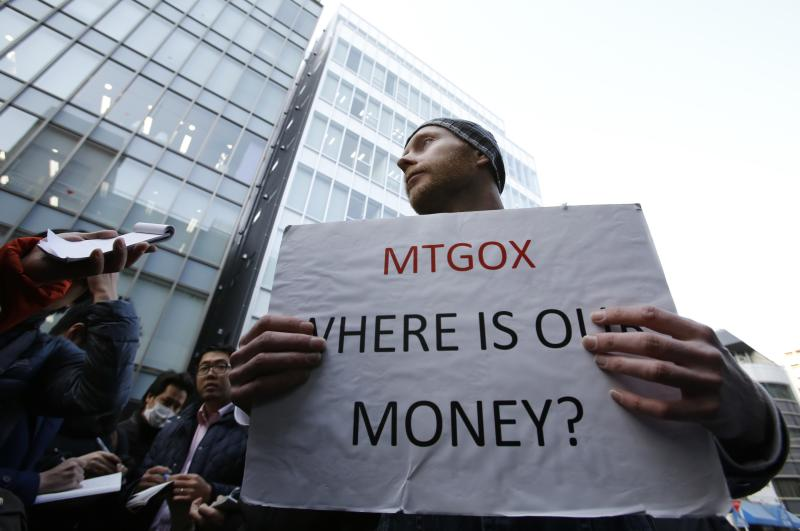 Kolin Burges, a self-styled cryptocurrency trader and former software engineer from London, holds a placard to protest against Mt. Gox, in front of the building where the digital marketplace operator was formerly housed in Tokyo February 26, 2014. Japanese authorities are looking into the abrupt closure of Mt. Gox, the top government spokesman said on Wednesday in Tokyo's first official reaction to the turmoil at what was the world's biggest exchange for bitcoin virtual currency. REUTERS/Toru Hanai (JAPAN - Tags: BUSINESS SCIENCE TECHNOLOGY CIVIL UNREST)