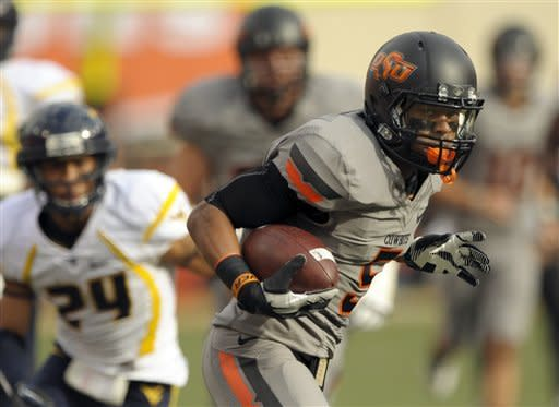 Oklahoma State receiver, Josh Stewart runs past West Virginia defenders for a touchdown during the first half of an NCAA college football game in Stillwater, Okla., Saturday, Nov. 10, 2012. (AP Photo/Brody Schmidt)