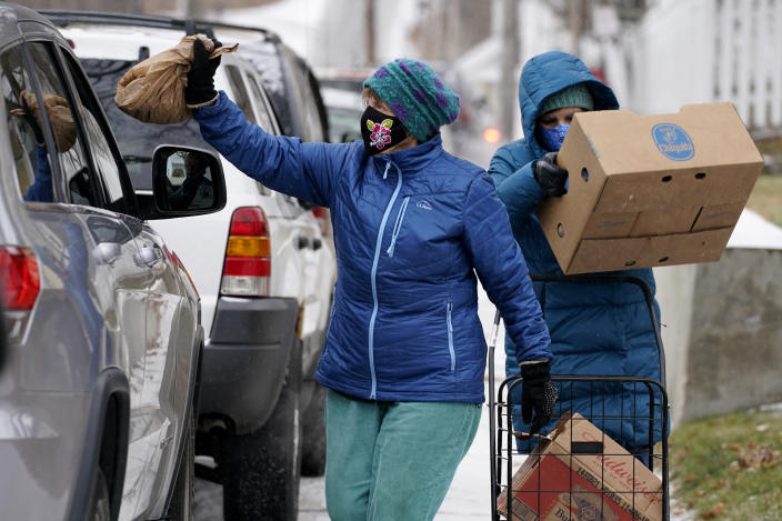 Joan Beal, left, and Mindy Butler wear face coverings to help prevent the spread of coronavirus while handing out pet food at a drive-thru food pantry outside the First Universalist Church, Wednesday, Nov. 25, 2020, in Norway, Maine. (AP Photo/Robert F. Bukaty)