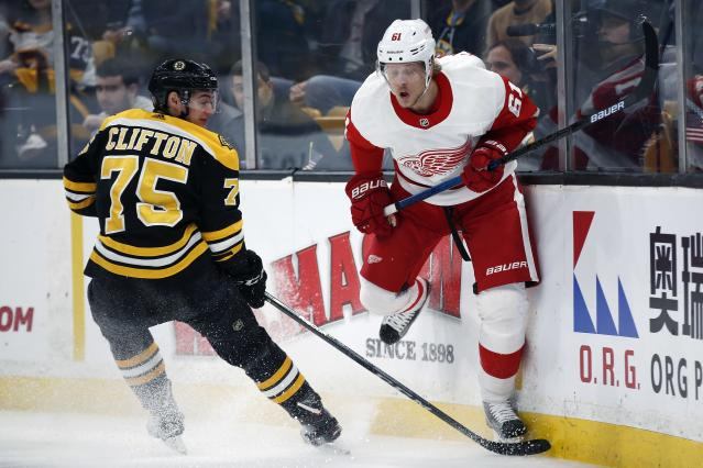 Detroit Red Wings' Jacob de la Rose (61) hits the boards while battling Boston Bruins' Connor Clifton (75) for the puck during the first period of an NHL hockey game in Boston, Saturday, Dec. 1, 2018. (AP Photo/Michael Dwyer)