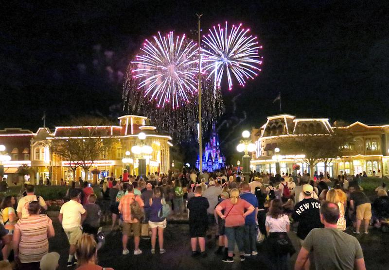 Guests gather on Main Street USA, in the Magic Kingdom at Walt Disney World, to watch fireworks before the park closed, Sunday night, March 15, 2020, in Lake Buena Vista, Fla. Walt Disney World announced that all their Florida parks will be closed for the rest of March as a result of the coronavirus pandemic. (Joe Burbank/Orlando Sentinel/Tribune News Service via Getty Images)