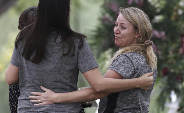 Women embrace during the funeral of Dawna Ray Langford, 43, and her sons Trevor, 11, and Rogan, 2, who were killed by drug cartel gunmen, at the cemetery in La Mora, Sonora state, Mexico, Thursday, Nov. 7, 2019. Three women and six of their children, related to the extended LeBaron family, were gunned down in an attack while traveling along Mexico's Chihuahua and Sonora state border on Monday. (AP Photo/Christian Chavez)