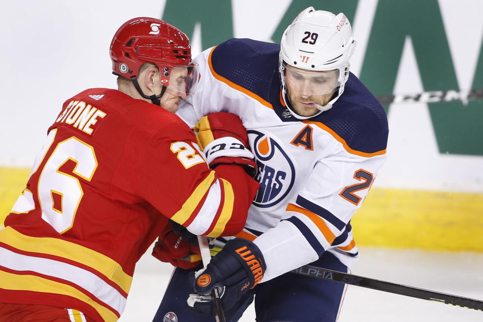 Calgary Flames' Michael Stone, left, runs into Edmonton Oilers' Leon Draisaitl during the first period of an NHL hockey game Saturday, April 10, 2021, in Calgary, Alberta. (Larry MacDougal/The Canadian Press via AP)