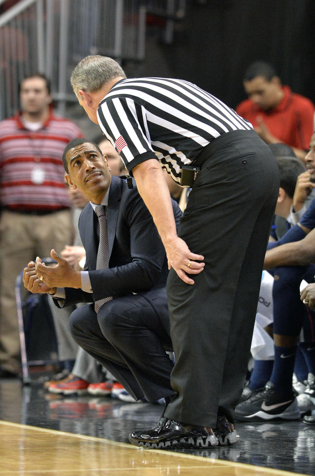 Connecticut head coach Kevin Ollie, left, talks with a referee during the first half of an NCAA college basketball game against Louisville, Saturday, March 8, 2014, in Louisville, Ky. (AP Photo/Timothy D. Easley)