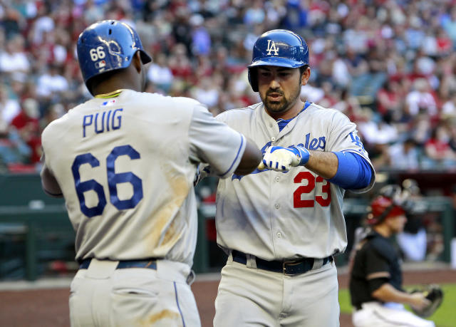 Los Angeles Dodgers' Adrian Gonzalez (23) is congratulated by teammate Yasiel Puig (66) after hitting a two-run home run against the Arizona Diamondbacks during the third inning of a baseball game on Saturday, April 12, 2014, in Phoenix. (AP Photo/Ralph Freso)