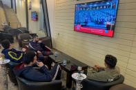 People watch Libya's parliament meet to vote on a unity government on a TV screen at a cafe in Misrata