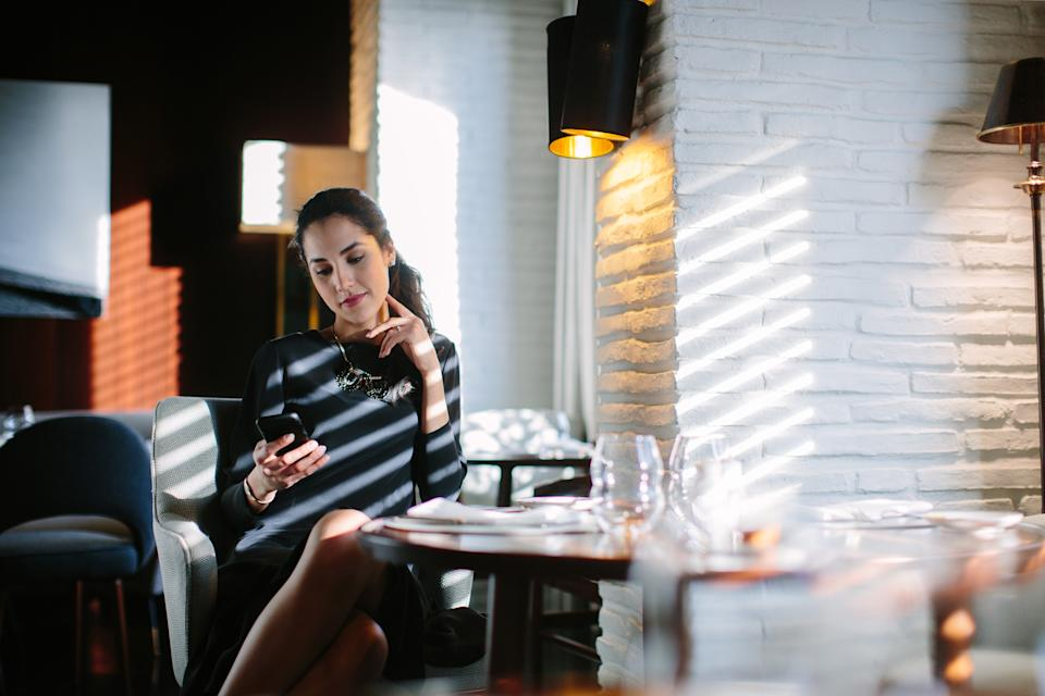 Picture of a sophisticated young woman reading a text on her smartphone in a boutique hotel restaurant.