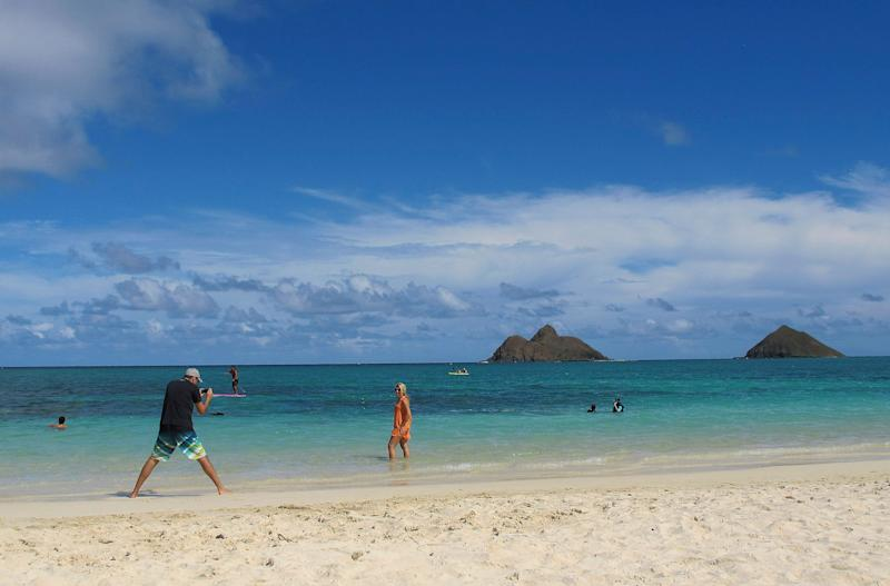"FILE - This Oct. 29, 2013 file photo shows tourists on Lanikai Beach in Kailua, Hawaii. Airbnb is pushing back against Hawaii's attempt to find tax delinquents by subpoenaing 10 years' worth of invoices, receipts and other records from the home-sharing platform's island hosts, calling it an unprecedented, ""massive intrusion"" that violates state and federal law. (AP Photo/Audrey McAvoy)"