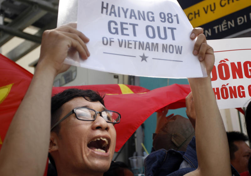 A Vietnamese protester holds up a placard and shouts slogans during a protest rally against China outside the Chinese Consulate in Ho Chi Minh City, Vietnam, Saturday, May 10, 2014. Around 100 people gathered and protested China's deployment of an oil rig in the disputed South China Sea, in the country's commercial capital. Vietnamese anger toward China is running at its highest level in years after Beijing deployed the oil rig in the disputed water. (AP Photo)